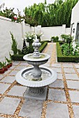 Tiered, antique-style fountain in narrow courtyard with geometric beds