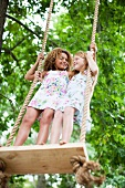 Smiling girls standing on tree swing
