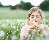 Girl smelling flowers in meadow