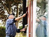 Older man painting side of house