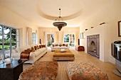 Helle Sofagarnitur und gepolsterte Couchtische in elegantem Wohnraum einer Landhausvilla