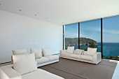 Modern living room with white furniture and ocean view