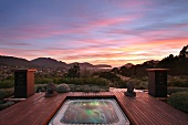Hot tub surrounded by wooden deck at sunset