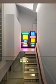 View of floating staircase treads and shelves of multi-coloured light boxes in designer apartment through glass balustrade