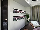 Illuminated niches in wall containing china vases on glass shelves behind sofa in elegant interior