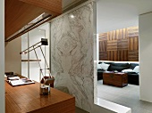 Marble wall dividing home office from living room
