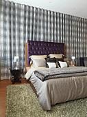 Elegant modern bedroom with purple velvet headboard