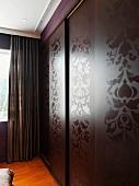 Einbaukleiderschrank mit glänzendem, floralem Muster auf matten Schiebetüren