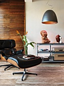 Classic 50s armchair with footstool and designer lamp in front of ethnic sculpture on hifi stand