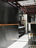 Bar stools at kitchen counter and black sliding wall in front of designer kitchen