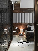 Bed with grey and black covers in front of wood-panelled wall and fitted wardrobe to one side with sliding doors