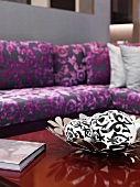 White spheres with black patterns in bowl with flower motif and purple patterned, classic modern sofa in blurred background