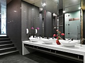 Long mirrored wall above oval washbasins and flower arrangements in Oriental washroom in dark shades