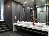 Spiegelfronten über ovalen Waschschüsseln und Blumenschmuck im dunkel getönten, asiatisch modernen Toiletten-Vorraum