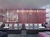 Huge sofas with grey scatter cushions in front of slatted partition in classic modern lounge area