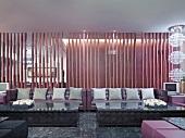 Megasofas mit grauen Kissen vor Lamellentrennwand in klassisch modernem Loungebereich