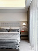 Doppelbett mit gepolstertem Kopfteil und grau gestreifter Bettwäsche in klassisch modernem Schlafzimmer