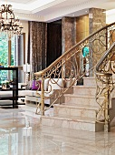 Marble staircase and decorated brass railing in the foyer of an elegant villa