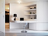 See-through shell chair in front of white multi-purpose furniture -- room partition with work surface and shelves
