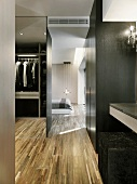Modern closet with parquet flooring next to a bedroom