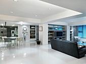 Moderner Wohn- und Essraum mit grauem Sofa auf glänzendem weissen Boden