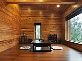 Asian tea room with floor pillows beside a low table made of dark wood in a wood paneled room with a large windows