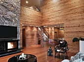 Minimalist living room with wood paneled walls and open fireplace under a TV on a natural stone wall
