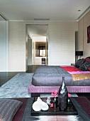 Doppelbett im modernen Schlafraum mit offener Ankleide