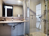 Vanity with stone tiles in front a a mirror next to a glass shower stall