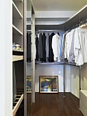 Gentlemen's clothes hanging up on rods in a modern dressing room