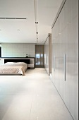Minimalist bedroom with built-in cupboards and illuminated, suspended ceiling panels