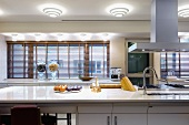Kitchen counter with fruit bowls next to kitchen utensils with a modern feel