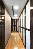 Moderner schmaler Flur mit Trennwand aus opakem Glas im Holzrahmen