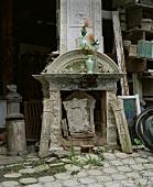 Antike Kaminelemente in offenem scheunenartigem Raum gelagert