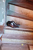 Men's shoes threaded with spaghetti shoelaces on vintage wooden stairs