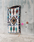 Rag rug made from old clothes hanging on concrete wall