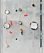 Wall plates and antique clocks connected by threads on concrete wall