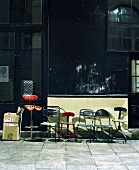 Various vintage metal chairs on pavement in front of shop