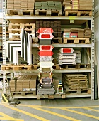 Metal warehouse shelves of wooden pallets and storage boxes next to modern nesting chairs