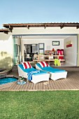 Small, Mediterranean bungalow with open glass wall and view into living area beyond; wooden terrace with upholstered loungers in foreground lend a summery holiday feeling