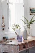 Console table with drawers and weathered white paint below window with interior shutters; various vases and containers of twigs from garden