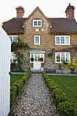 Gravel front path edged in box leading to old, English country house with brick facade and white lattice windows