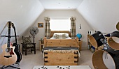 Youthful, country-house style in attic bedroom with wooden bed, guitar stand and drum kit