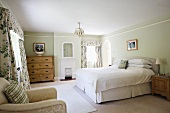 Double bed with upholstered headboard, rustic wooden cabinets and floral curtains with pelmets in spacious, country-house bedroom