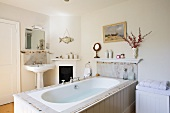 Bathtub accessible from three sides clad in white-painted wood and pedestal sink next to small fireplace