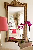Reflection of pale, country-house living room in mirror with antique gilt frame; pink lampshade and orchids in foreground: feminine atmosphere