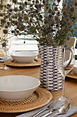 Festively set table with bouquet of dried flowers in decorative blue and white ceramic jug and white soup bowls on basketwork table mats