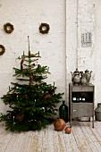 Weihnachtsbaum mit brennenden Kerzen neben Vintage Schränkchen vor weisser Wand in rustikalem Ambiente