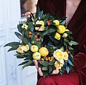 Wreath of leaves and fruit held by woman in festive clothing