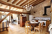 Kitchen and dining area under historical roof structure of open-plan interior